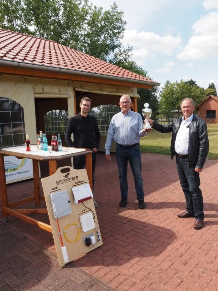 v.l. David Schäper und Eckhard Nelles nehmen Pokal und Spende von GREENFIBER Geschäftsführer Uwe Krabbe entgegen. Foto: Hinrich Bernzen